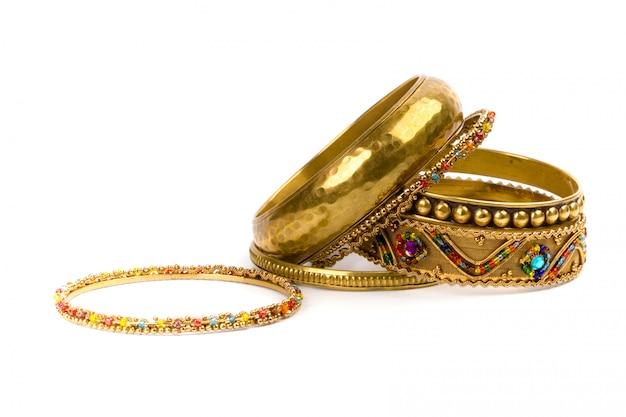 Pile de bracelets dorés isolés sur fond blanc Photo Premium