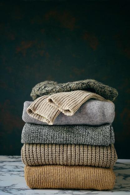 Pile de chandails tricotés confortables. concept automne-hiver, pulls en laine tricotés. tas de vêtements d'hiver tricotés, chandails, tricots Photo gratuit