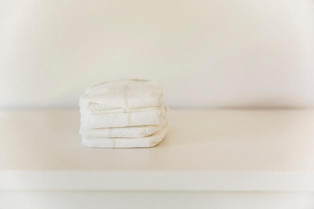 Pile de couche sur table contre mur Photo gratuit