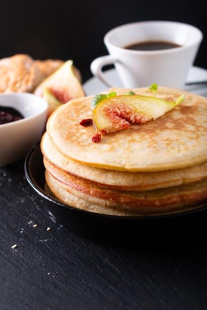 Pile de crêpes bio maison avec petit-déjeuner aux figues sur fond noir Photo Premium