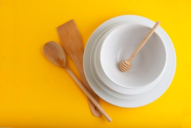 Pile de différentes assiettes blanches, bols. isolé sur fond jaune Photo Premium
