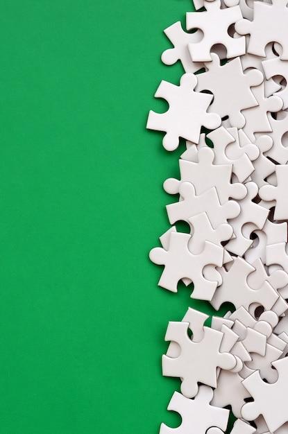 Une pile d'éléments non peignés d'un puzzle blanc repose sur une surface verte Photo Premium