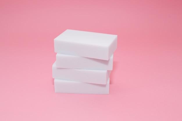 Pile d`éponges domestiques en mélamine avec quatre éponges pour le nettoyage sur fond rose. Photo Premium