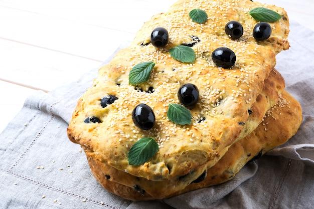 Pile de focaccia au pain italien traditionnel avec olives, ail et herbes Photo Premium