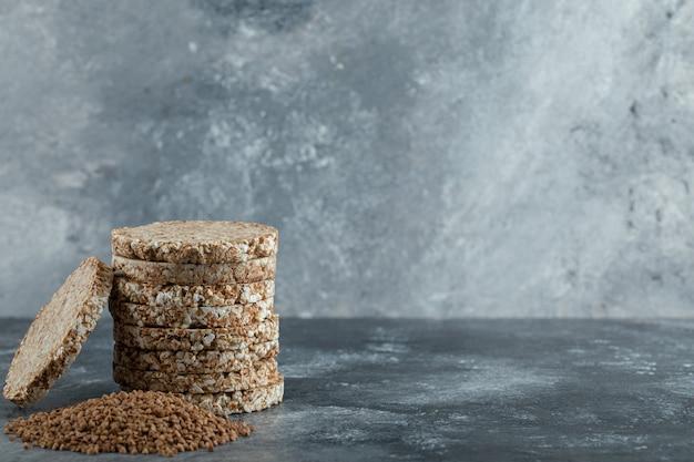 Pile De Gâteaux De Riz Et Tas De Sarrasin Sur La Surface En Marbre Photo gratuit
