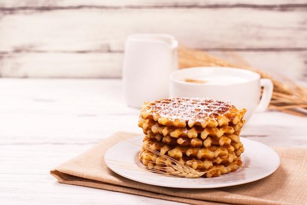 Pile de gaufres belges épaisses avec du sucre en poudre et une tasse de café cappuccino. Photo Premium