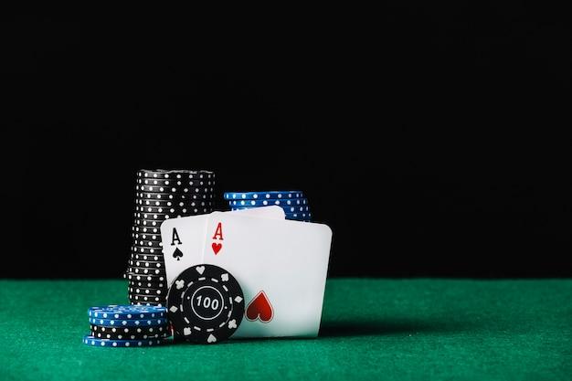 Pile de jetons de casino bleu et noir avec des as de cœur et de pique Photo gratuit