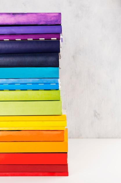 Pile de livres arc-en-ciel coloré sur fond blanc. espace de copie Photo Premium