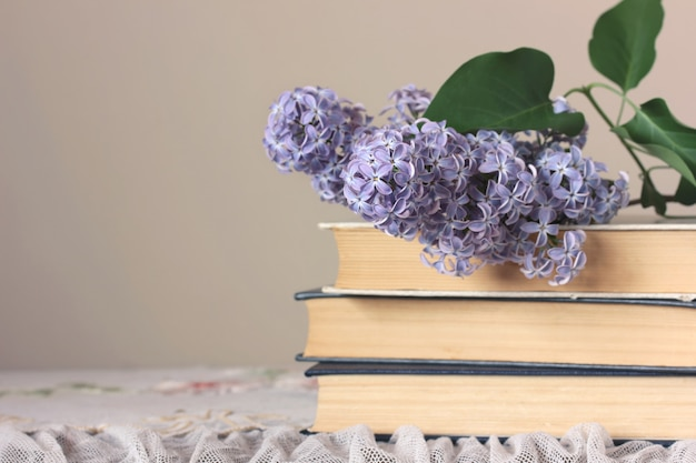 Pile de livres et une branche de lilas en fleurs sur la table sur un fond de carte. Photo Premium
