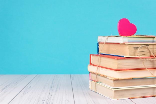 Pile de livres et coeur rose Photo Premium