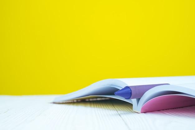 Pile de livres et de crayons de cire colorés à la cire colorée avec fond jaune. Photo Premium