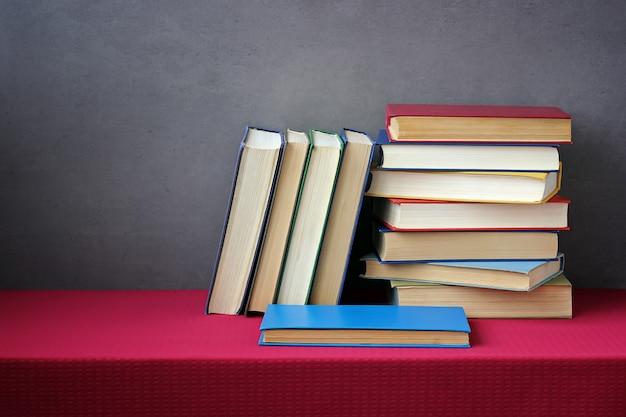 Une pile de livres dans les couvertures colorées sur la table avec une nappe rouge. nature morte avec des livres. Photo Premium