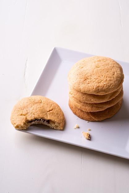 Pile Maison De Biscuits Sablés Au Chocolat Avec Un Biscuit Mordu Sur Une Table En Bois Plaque Blanche Photo Premium