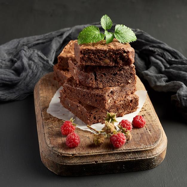 Pile de morceaux carrés de gâteau au brownie au chocolat sur une planche à découper en bois marron Photo Premium