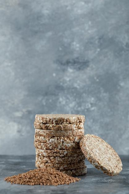 Pile De Pain Croustillant Et Tas De Sarrasin Sur La Surface En Marbre Photo gratuit