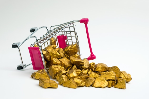 Pile de pépites d'or ou de minerai d'or dans le caddie de panier ou de supermarché sur fond blanc, pierre précieuse ou un morceau de pierre dorée, concept financier et commercial. Photo Premium