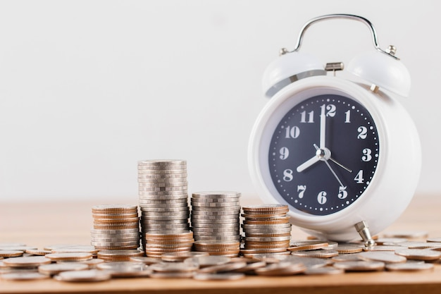 Pile de pièces avec horloge pour économiser de l'argent Photo Premium