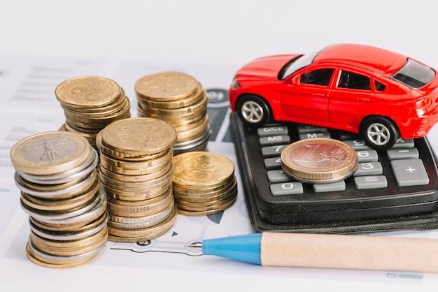 Pile de pièces de monnaie; calculatrice; voiture jouet et stylo sur le gabarit Photo gratuit