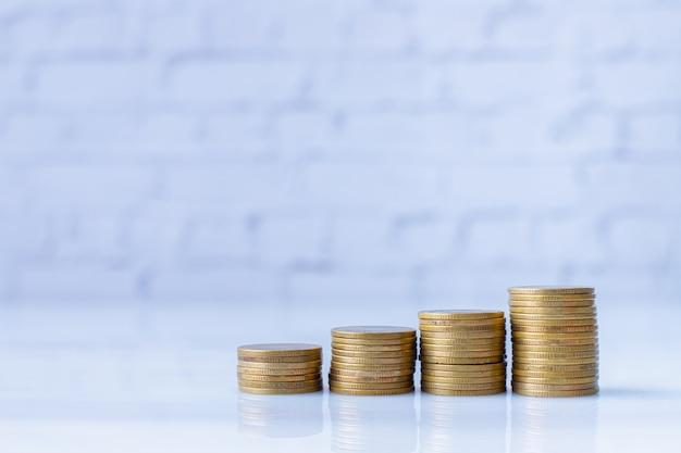Pile de pièces d'or sur le mur de briques blanches Photo Premium