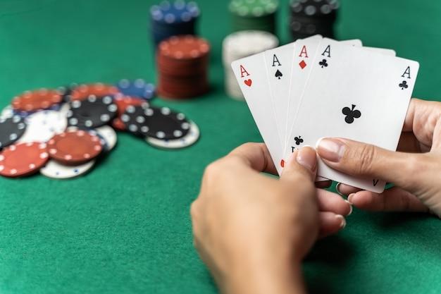 Pile de puces et main de femme avec quatre as sur la table. concept de jeu de poker Photo Premium