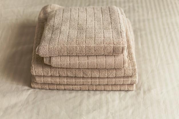 Pile de serviette d'hôtel beige sur le lit à l'intérieur de la chambre. vintage tonifiant Photo Premium