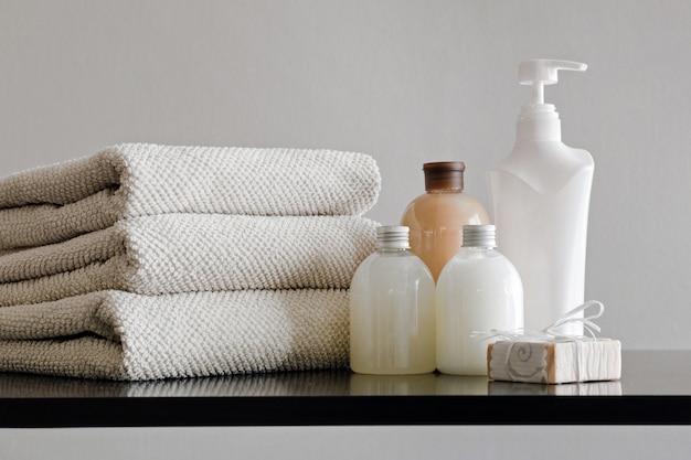 Pile de serviettes, bouteilles avec shampoing, lotion pour le corps, lait de douche et savon à la main sur fond neutre. Photo Premium
