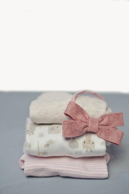 Pile de vêtements plié coton coloré sur fond d'espace de table blanche, linge de bébé. Photo Premium