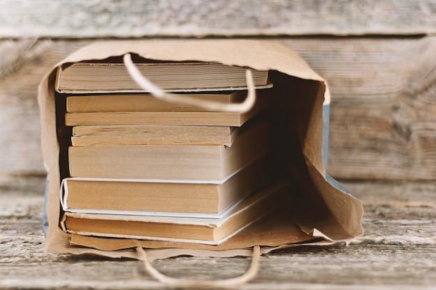 Pile de vieux livres dans un sac en papier sur fond en bois Photo Premium