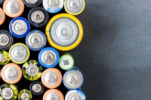 Piles Alcalines Usagées De Différentes Tailles Sur Fond Noir Photo Premium