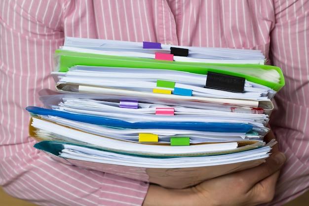 Piles de documents dans des dossiers papier en mains, documents de rapport d'activité. Photo Premium