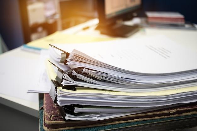 Piles de documents inachevés de dossiers papier sur le bureau pour les documents de rapport, des piles de feuilles de papier inachevées atteint avec des clips d'intérieur, concept de bureaux d'affaires. le document est écrit, dessiné, présenté. Photo Premium