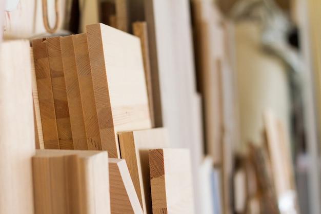 Des piliers en bois et des planches épaisses dans l'atelier du meuble sont prêts à travailler Photo Premium