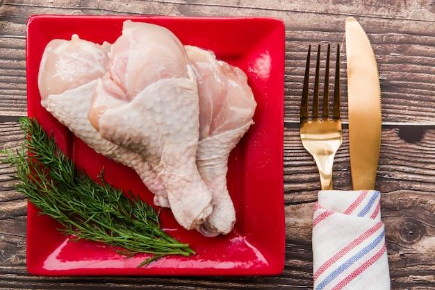 Pilons de poulet crus à l'aneth frais dans une assiette avec une fourchette et un couteau à beurre Photo gratuit