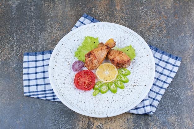 Pilons De Poulet Grillé Sur Plaque Blanche Avec Des Légumes. Photo gratuit