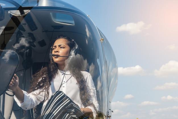 Pilote dans le cockpit de l'hélicoptère avant le décollage. pilote d'hélicoptère de jeune femme. Photo Premium