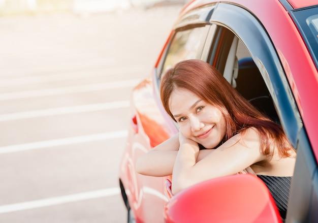 Pilote de femme asiatique en voiture rouge Photo Premium