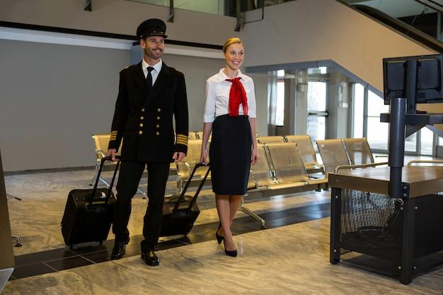 Pilote Et Hôtesse De L'air Marchant Avec Leurs Sacs à Roulettes Photo gratuit