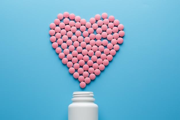 Pilules b12 roses en forme de coeur sur fond bleu Photo Premium