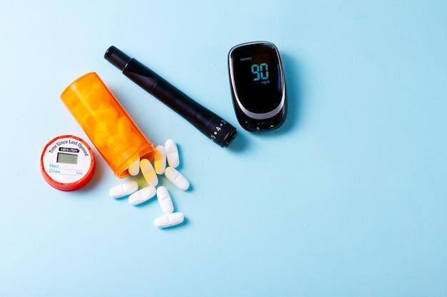 Pilules Blanches Dans Une Bouteille Médicale Orange Avec Lecteur De Glycémie Sur Fond Bleu Avec Espace De Copie Photo Premium