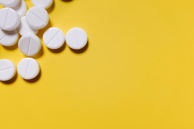 Pilules blanches sur un fond jaune. le concept de médecine, pharmacie et santé. Photo Premium