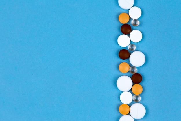 Les pilules et les capsules multicolores sont disposées sur un fond bleu dans une rangée Photo Premium
