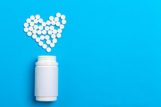Pilules coeur en bouteille de pilules sur fond bleu, vue de dessus Photo Premium