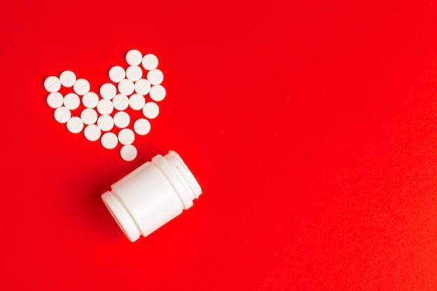 Pilules de coeur en bouteille de pilules sur fond rouge, vue de dessus Photo Premium