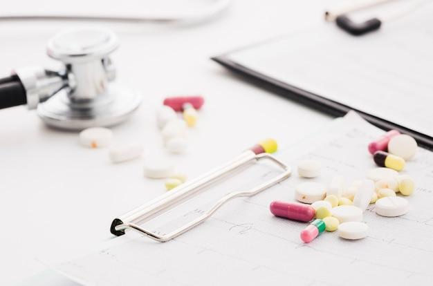 Pilules colorées sur le graphique et le stéthoscope ecg sur fond blanc Photo gratuit