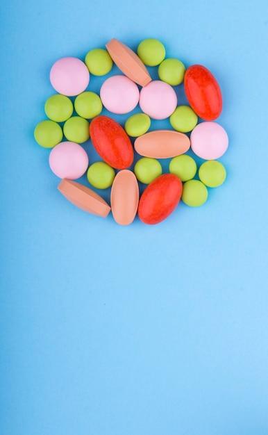 Pilules, Comprimés Et Gélules De Couleur Sur Un Tableau Bleu. La Médecine Et La Santé. Photo Premium