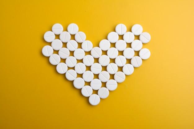 Pilules en forme de coeur sur fond jaune. lay plat, vue de dessus. Photo Premium