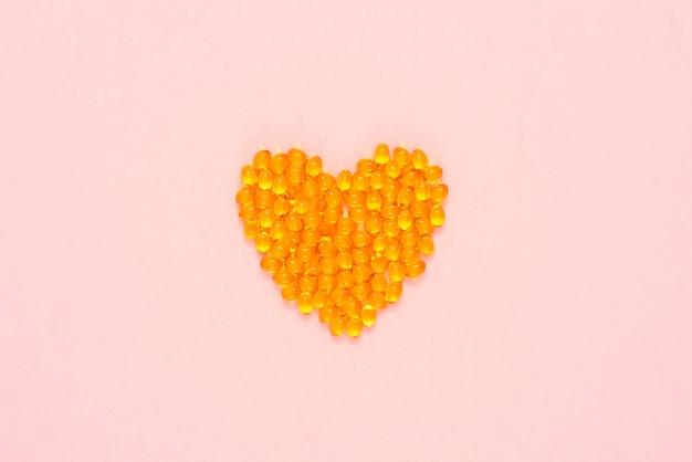 Pilules jaunes disposées en forme de coeur Photo Premium