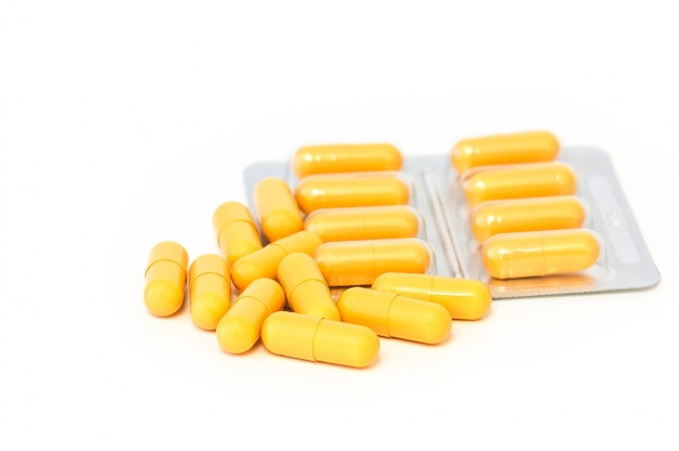 Pilules jaunes vives et des cloques dispersées sur un fond blanc. Photo Premium