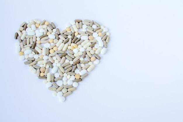 Pilules médicales colorées en vrac sur un fond blanc. Photo Premium