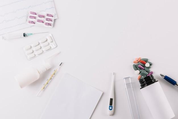Pilules médicales; seringue et thermomètre isolé sur fond blanc Photo gratuit